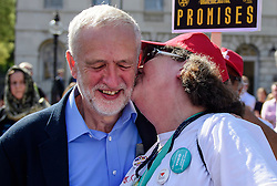 © Licensed to London News Pictures. 13/09/2016. London, UK.  Labour Party leader JEREMY CORBYN is given a kiss by a supporter while attending a rally outside the Parliament in London for the Orgreave Truth and Justice Campaign, which calls for a public inquiry into the June 1984 confrontation between police and pickets at the British Steel Corporation coking plant in Orgreave, South Yorkshire. Photo credit: Ben Cawthra/LNP