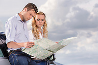 Couple reading map while leaning on car against cloudy sky