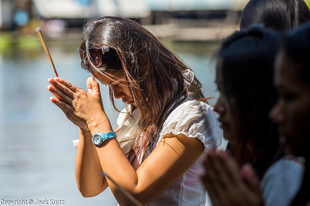 03 JANUARY 2013 - BANGKOK, THAILAND: A woman prays before releasing fish into Phra Khanong canal to make merit at Wat Mahabut. Just a few minutes from downtown Bangkok, the neighborhoods around Wat Mahabut interlaced with canals, still resemble the Bangkok of 60 years ago. Wat Mahabut is a large temple off Sukhumvit Soi 77. The temple is the site of many shrines to Thai ghosts. Many fortune tellers also work on the temple's grounds.   PHOTO BY JACK KURTZ