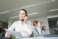 Smiling young businesswoman holding documents while using landline phone with colleagues in background at office