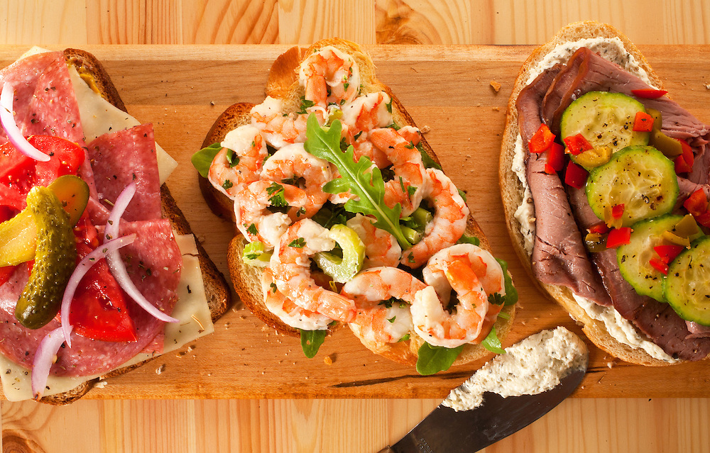 Open face sandwiches,Salami,tomato,cheese,pickles on hearty multi grain bread,Shrimp salad open faced sandwich,Roast beef with cucumber salad open faced sandwich,sitting on long narrow cutting board