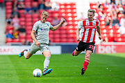 Ross McCrorie (#15) of Portsmouth FC crosses he ball as Grant Leadbitter (#23) of Sunderland AFC watches on during the EFL Sky Bet League 1 match between Sunderland and Portsmouth at the Stadium Of Light, Sunderland, England on 17 August 2019.