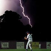 Pitcher Adam Meinershagsen on the mound for the Sydney Blues baseball team during a lightning storm at Parramatta Stadium, Sydney, Australia.