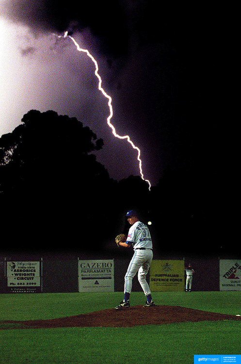 Pitcher Adam Meinershagsen on the mound for the Sydney Blues baseball team during a lightning storm at Parramatta Stadium, Sydney, Australia.