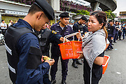 27 MAY 2014 - BANGKOK, THAILAND: A woman hands canned soft drinks and energy drinks to Thai soldiers stationed at Victory Monument. It's not unusual for supporters of the military to bring flowers and drinks to soldiers stationed on the street. Authorities announced Tuesday that at least one beverage given to a soldier was tampered with and poisoned. An investigation into the tampered drink is ongoing. Several hundred people protested against the coup in Bangkok at Victory Monument. It was the fourth straight day of pro-democracy rallies in the Thai capital as the army continued to tighten its grip on Thai life. The protest Tuesday was the smallest so far.     PHOTO BY JACK KURTZ
