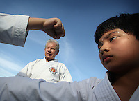 Karate coach Vicente Gonzalez, center, observes the ten years old John Paulo's training session at Sunset Lake Community Center on Monday July 6, 2009. Staff photo/Cristobal Herrera..