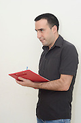 Mail Industrial Engineer in his thirties takes notes with a clipboard