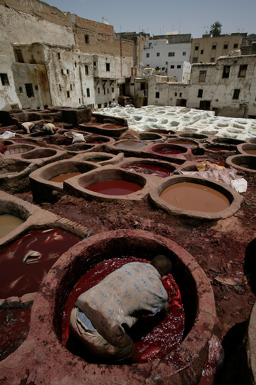 Fez Tannery is a good example of mass production, a process that we often consider as being modern. The workers stand in the stone vessels arranged like honeycombs, filled with different dyes, dying the arms and legs of the men. The hides are first soaked in diluted acidic pigeon excrement and then transferred to other vessels containing vegetable dyes such as henna, saffron and mint. When the dying process has been completed the hides are dried on the roofs of the Medina or other close situated Morocco property roofs. Traditionally natural dyes were used, although some tanneries now use artificial dyes. The traditional tanneries get the red color from poppies, yellow from saffron, brown from henna, and green from wild mint.