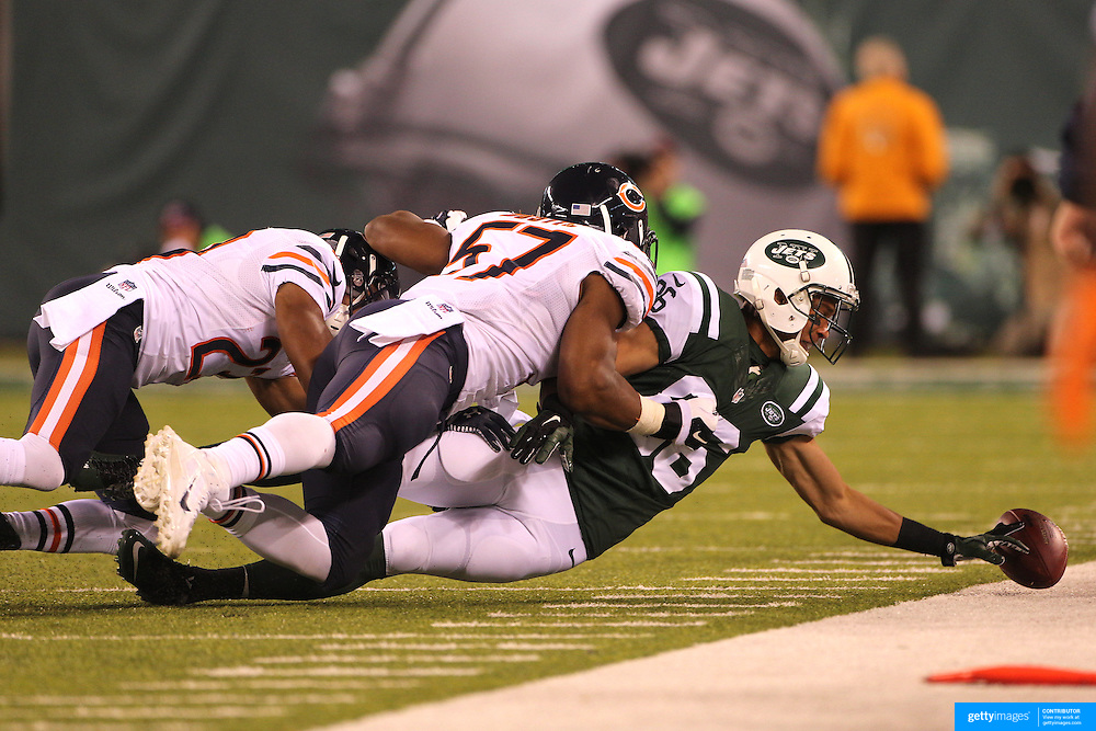 David Nelson, New York Jets, drops the ball as he is tackled by Kyle Fuller and Jonathan Bostic, Chicago Bears, during the New York Jets Vs Chicago Bears, NFL regular season game at MetLife Stadium, East Rutherford, NJ, USA. 22nd September 2014. Photo Tim Clayton for the New York Times