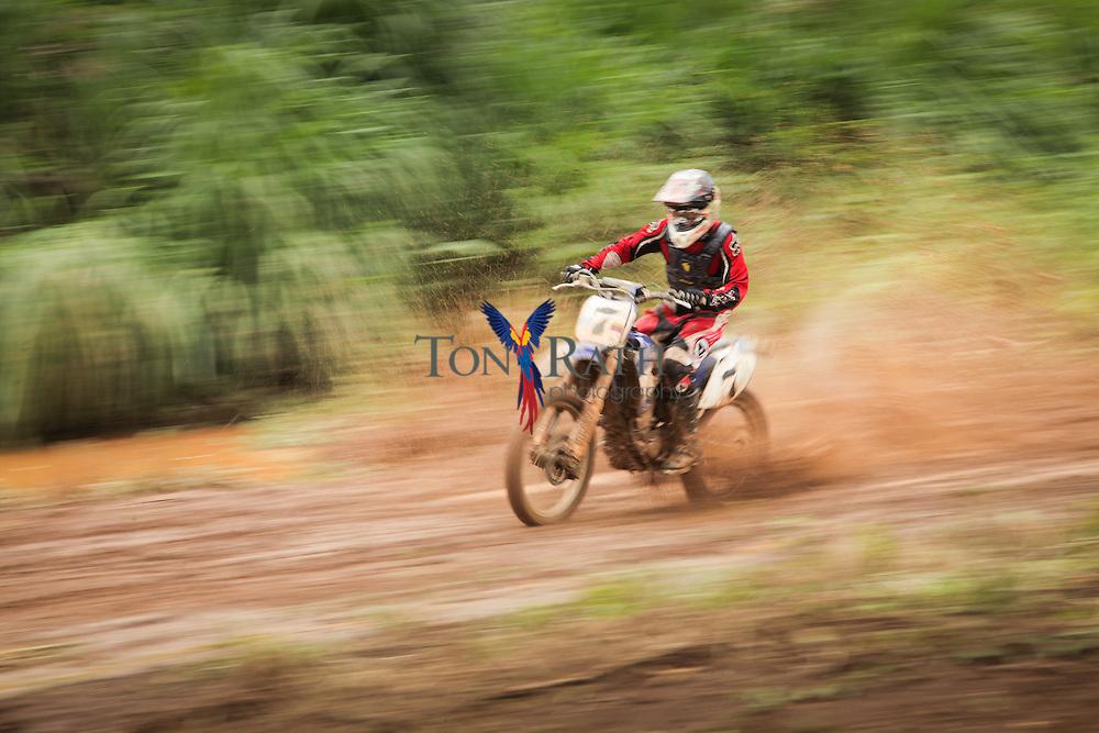 Panning shot shows single male motocross biker racing on clay outdoor trail sending mud splatters flying into the air in Belmopan, Belize.