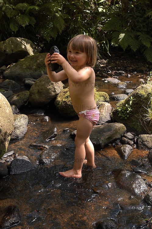 3 year old girl playing in stream