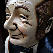 close-up of wooden Folk Art of waiter's face in front of restaurant
