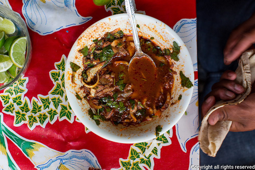 Barbacoa (beef stewed in chilies) served with tortilla and lime. Puesto de Barbacoa, Abastos Market, Oaxaca, Mexico Feb 8, 2014