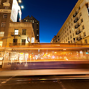 Intersection of Powell and Ellis Streets in the Union Square area of downtown San Francisco, CA. Streetcar traffic motion blur at dusk.