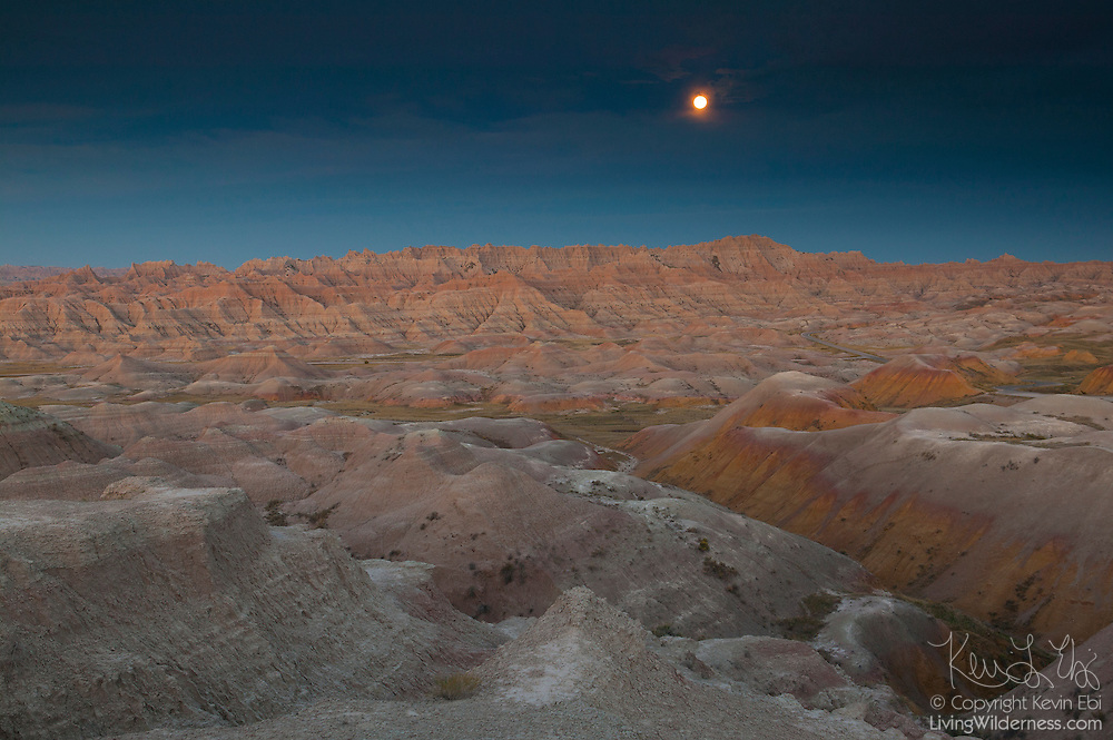 The full moon shines over the Conata Basin, located in Badlands National Park, South Dakota. Badlands National Park protects nearly 250,000 acres of sharply eroded buttes, pinnacles, and spires, as well as the largest protected mixed grass prairie in the United States.
