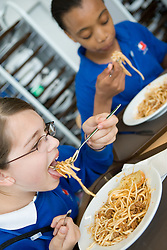 Secondary School students eating spaghetti Bolognese in the Restaurant,