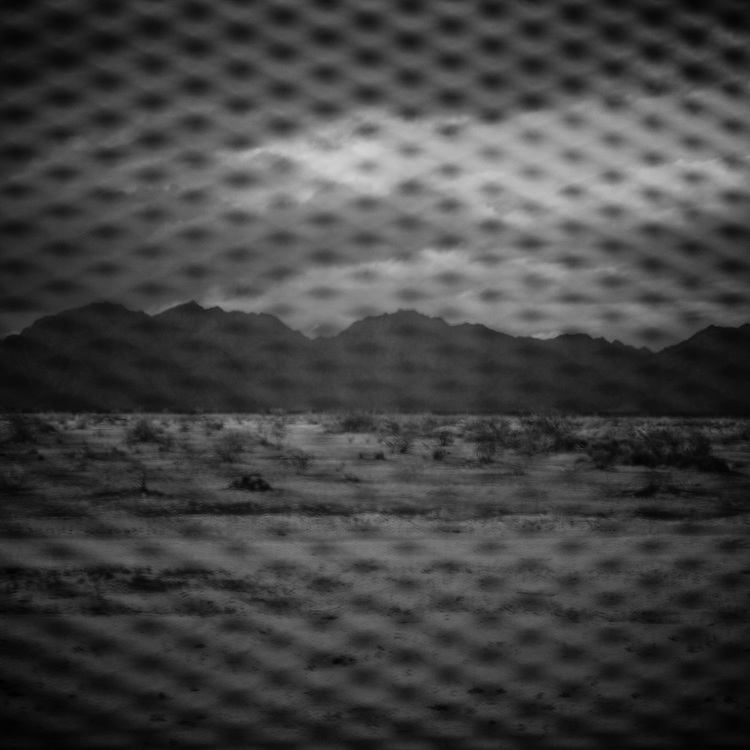 Mountains in the United States are seen from the Sonoran Desert in Mexico through the fence marking the border between the two countries in on Sunday, Feb. 3, 2008.