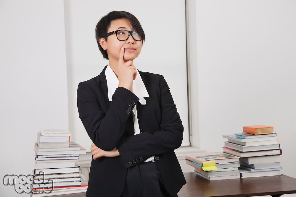 Thoughtful young businesswoman with stack of books on desk in office