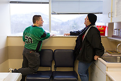 1/27/15 10:21:24 AM -- Louisa, KY, U.S.A  -- Cheryl Castle, right, plays a game of Eye Spy with her son Nate as they wait to be seen by Dr. Mazen Jaafar at his office in Prestonsburg on Tuesday. Nate had a low grade fever and a cough but was not in school because of inclement weather.<br /> <br /> Cheryl is a recent recipient of the high-tech device, can now do many tasks she was unable to do when her epileptic seizures became more severe and more frequent. Now she's getting back to a normal life.<br /> <br />  --    Photo by Jonathan Palmer, Freelance