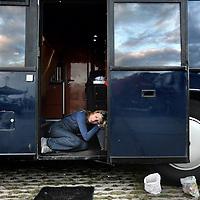 Nederland, Amsterdam , 1 oktober 2014.<br /> De rij caravans met mensen die een zelfbouwkavel willen kopen op het Zeeburgereiland wordt steeds groter.<br /> Sommige staan al een paar weken in de wachtrij totdat ze een kavel mogen kopen. Pas volgende week zaterdag gaan de kavels pas in de verkoop, maar wie weg gaat, verliest zijn plek in de rij.<br /> Een van de kampeerders staat er al een tijdje in zijn caravan: 'Ik ben hier behoorlijk vroeg gaan staan, want er is &eacute;&eacute;n kavel waar ik echt ge&iuml;ntresseerd in ben. Er hoeft er maar een eerder te zijn en dan ben je 'm kwijt.'<br /> De wachtende kopers vinden het best gezellig op het terrein: 'Je ontmoet een soort van je toekomstige buren als het zo doorgaat. Dat geeft een apart campinggevoel en we barbecuen samen.'<br /> Een probleempje, als je weggaat ben je je plek kwijt. 'Als je moet werken moet je zorgen dat er iemand anders op je plek zit. Ik had hier eerst helemaal geen zin in, maar het is toch wel een bizar avontuur.'<br /> Op de foto: een doodvermoeide potentiele kavelkoper slaapt in de deuropening van haar bus.<br /> Foto:Jean-Pierre Jans