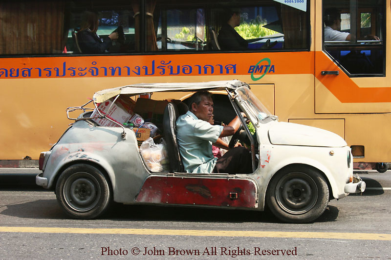 A fully loaded old jalopy (car) and a modern BMTA (Bangkok Metropolitan Transit Authoriy) bus share a street in Bangkok, Thailand.