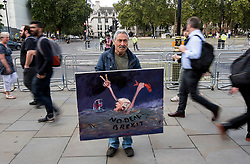 © Licensed to London News Pictures. 04/09/2019. London, UK. Satirical artist KAYA MAR holds up a painting outside the Houses of Parliament in Westminster, London. British Prime Minister Boris Johnson has a called for a general election after losing his first commons vote and losing his majority, removing his control of parliament. Photo credit: Ben Cawthra/LNP