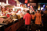 Shoppers pass stalls selling meat kebabs and corn on the cobs in the Night Market, Wangfujing Street, Beijing, China