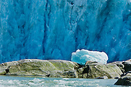 An iceberg rests on the top of boulders after being tossed on shore by the tidal wave from calving Dawes Glacier in the background in Endicott Arm fjord in the Inside Passage of Southeast Alaska. Summer. Morning.