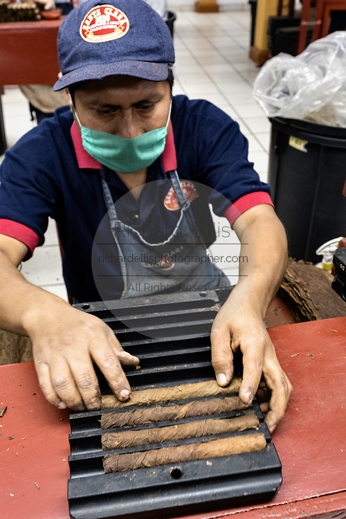 A cigarmaker called a torcedor places rolled fine cigar into a wooden mold for pressing at the Santa Clara cigar factory in San Andres Tuxtlas, Veracruz, Mexico. The factory follows traditional hand rolling using the same process since 1967 and is considered by aficionados as some of the finest cigars in the world.