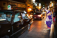 Geisha says goodbye to occupants of a taxi in Hanamikoji dori street.Geisha's distric of Gion.Kyoto. Kansai, Japan.