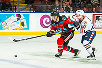 KELOWNA, BC - OCTOBER 12: Ryan Hughes #21 of the Kamloops Blazers back checks Sean Comrie #3 of the Kelowna Rockets as he skates with the puck at Prospera Place on October 12, 2019 in Kelowna, Canada. (Photo by Marissa Baecker/Shoot the Breeze)