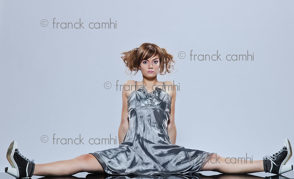 beautiful young caucasian woman girl evening dress sitting on the floor on studio isolated plain background