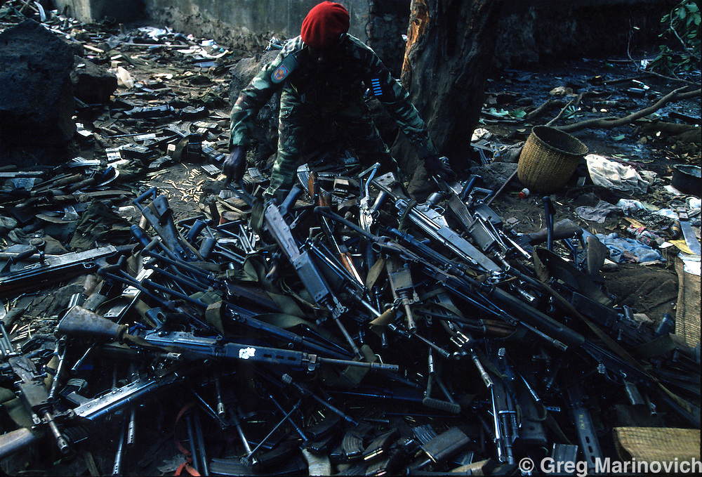 Goma, Zaire, A Zairean soldier collects semi automatic rifles, Belgian FNs and South African R4s at a border crossing where millions of Hutus fled ahead of the Tutsi RPF takeover that followed and stopped the genocide of Rwandan Tutsis and Hutu moderates by extremist Hutus. 1994. Greg Marinovich