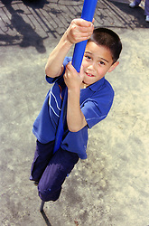 Young boy climbing down metal pole in children's playground,