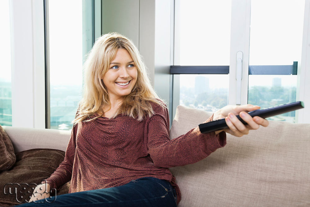 Smiling young woman watching television on sofa at home