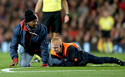 Stewards attempt to remove pitch invaders during the match