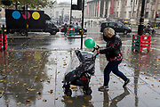 A mother with a green balloon walks past a film industry delivery van during heavy rainfall on an autumn afternoon in Trafalgar Square, on 24th October 2019, in Westminster, London, England.