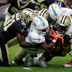 Aug 29, 2019; New Orleans, LA, USA; Miami Dolphins running back Mark Walton (9) is tackled by New Orleans Saints defensive back Chris Banjo (31) and running back Michael Burton (46) during a preseason game at the Mercedes-Benz Superdome. Mandatory Credit: Derick E. Hingle-USA TODAY Sports