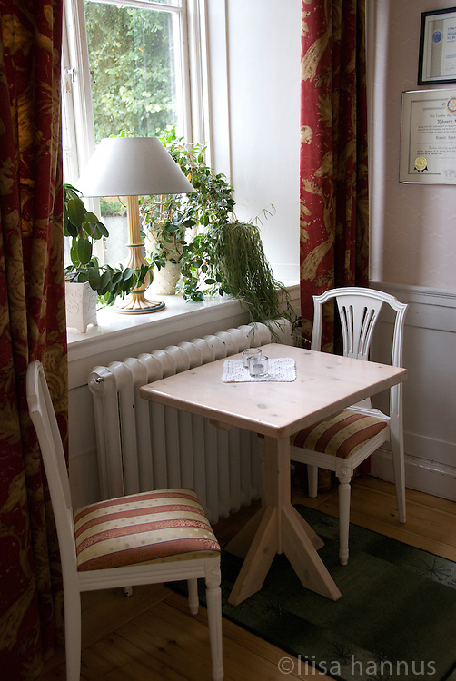 A table and two chairs are placed in front of a tall window on the ground floor of the main house at Taxinge Slott, or Palace, south of Stockholm, Sweden.