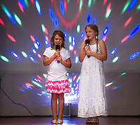 "Molly Hagan and Leanna Rowley sing ""Blank Space"" on stage during the Holy Trinity School talent show on Tuesday afternoon.  (Karen Bobotas/for the Laconia Daily Sun)"