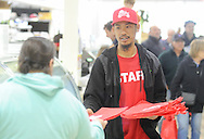 Tony Chang hands out shopping bags from the mart, during the grand reopening of the Columbus Farmers Market Saturday May 21, 2016 in Columbus, New Jersey. (Photo by William Thomas Cain)