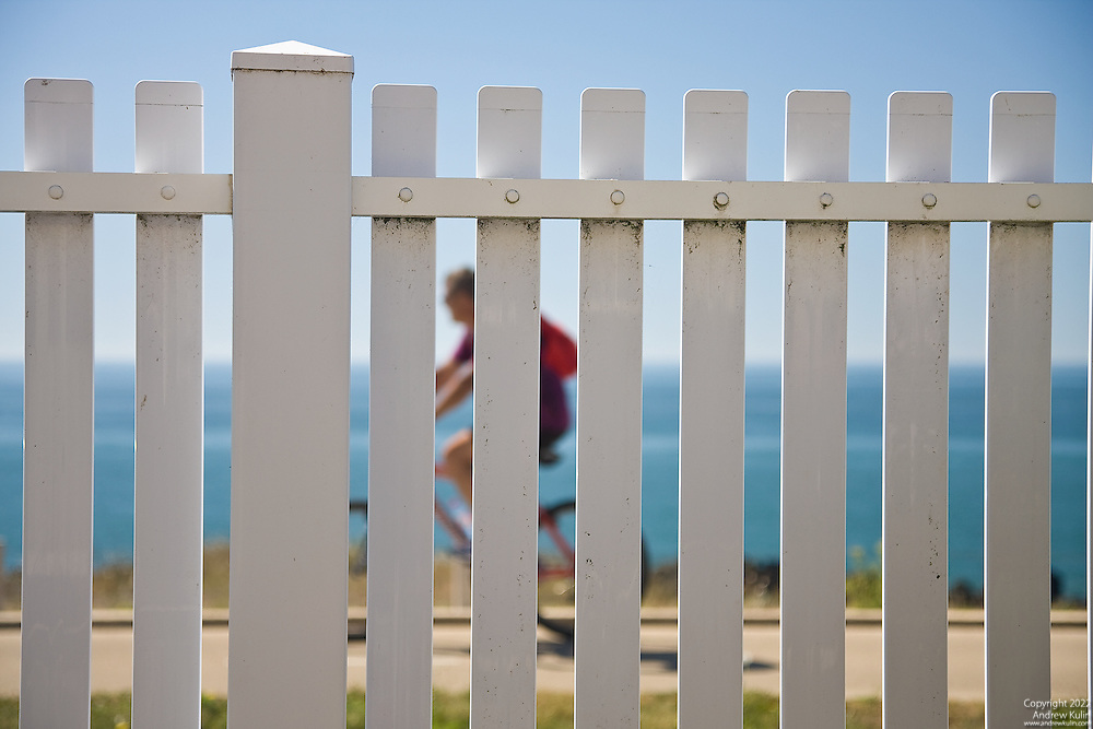 A cyclist along the Brittany shoreline seen through a white picket fence.