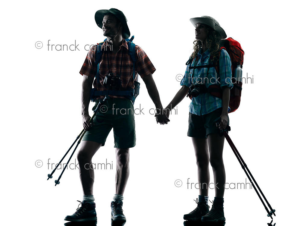 one caucasian couple trekker trekking nature in silhouette isolated on white background