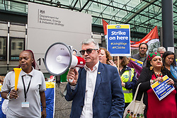 London, UK. 15 July, 2019. Mick Cash, General Secretary of the RMT trade union, addresses catering and cleaning staff belonging to the PCS trade union and outsourced to work at the Department for Business, Energy and Industrial Strategy (BEIS) via contractors ISS World and Aramark on the picket line outside the Government department after walking out on an indefinite strike for the London Living Wage, terms and conditions comparable to the civil servants they work alongside and an end to outsourcing.