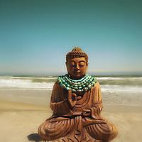 A buddha on a sandy beach