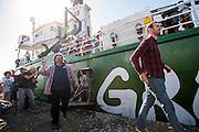 Beamnningslid Gizem Akhan, actievoerder Roman Dolgov en videojournalist Kieron Bryan van de Artic 30 die gevangen zijn genomen tijdens hun actie tegen Gazprom verlaten de Arctic Sunrise in Amsterdam. In IJmuiden is de Arctic Sunrise, het schip van milieuorganisatie Greenpeace dat een jaar door Rusland in beslag is genomen, aangekomen. De voormalige ijsbreker wordt in Amsterdam uit het water gehaald en opgeknapt omdat het gehavend is geraakt toen het aan de ankers lag. De boot van de milieuorganisatie is september 2013 door de Russen ge&euml;nterd en de bemanningsleden vastgezet op verdenking van piraterij. Greenpeace voerde actie bij een boorplatform in de Barentszzee. Als het schip weer is gerepareerd, wil de milieubeweging weer campagnes houden met de Artic Sunrise.<br /> <br /> In IJmuiden, the Arctic Sunrise, the Greenpeace ship that a year ago is seized by Russia, arrived. The former ice breaker is removed from the water in Amsterdam and refurbished since it was damaged when it was up to the anchors. The boat of the environmental organization is boarded in September 2013 by the Russians and the crew put down on suspicion of piracy. Greenpeace campaigned on a drilling platform in the Barents Sea. If the ship is repaired, the environmental movement wants to use the Arctic Sunrise again for campaigning.