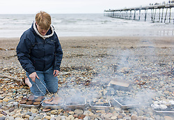 © Licensed to London News Pictures. 01/06/2013<br /> <br /> Saltburn, Cleveland, United Kingdom<br /> <br /> A woman prepares a barbecue on the first day of summer on the beach at Saltburn by the sea in Cleveland.<br /> <br /> Photo credit : Ian Forsyth/LNP