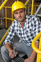 Portrait of young male worker with wrench sitting on steps at industry
