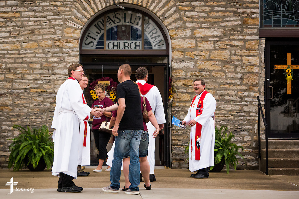 "The Rev. Timothy Mueller, pastor of St. John's Lutheran Church, greets visitors and parishioners before worship on Sunday, August 9, 2015, during a ""Day of Thanksgiving and Rededication""  at the church in New Minden, Ill. Nearly two years ago, a tornado damaged the church and surrounding homes. Mueller is joined by his son, the Rev. Jacob Mueller of Holy Cross Lutheran Church in Emma, Mo., the Rev. Dr. Matthew C. Harrison (center, facing away from camera), president of The Lutheran Church–Missouri Synod, and the Rev. Dr. Herbert C. Mueller Jr. (far right), first vice-president of the LCMS. LCMS Communications/Erik M. Lunsford"
