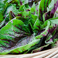 Purple and green amaranth greens in a basket at a farmers market.